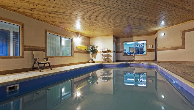 Indoor pool area with towel rack and chair