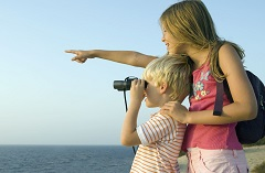 A boy with binoculars and a girl overlooking the ocean