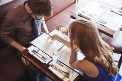 A couple looks over a menu at a restaurant dining table