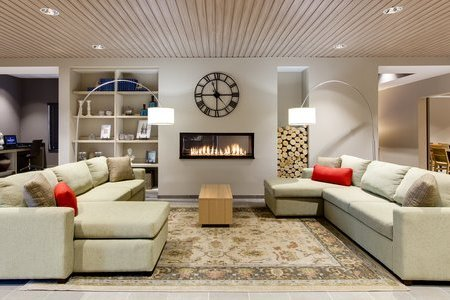 Spacious hotel lobby with two beige sectionals and a roaring fireplace