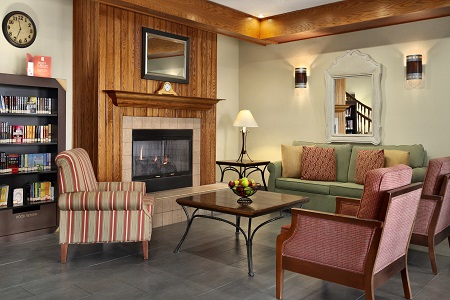Inviting lobby with fireplace, patterned chairs and a sofa