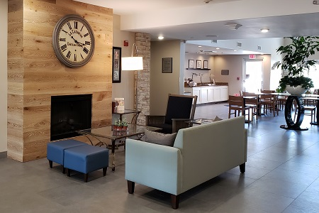 Welcoming lobby with a fireplace, couch and chair