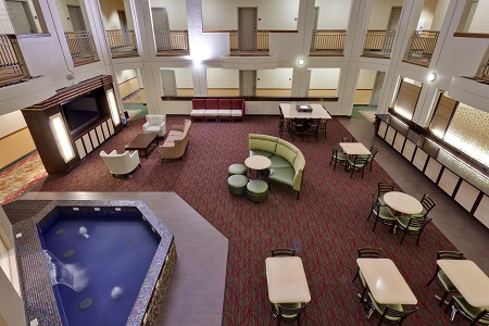 Spacious hotel atrium with dining tables and water feature