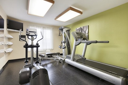 Fitness center with treadmill, elliptical and green accent wall