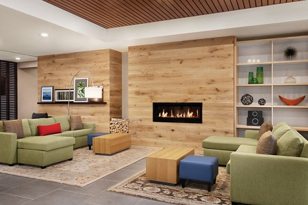 Hotel lobby with two green sectionals and a fireplace