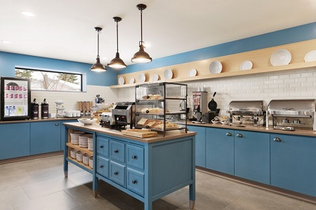 Breakfast servery with blue cabinets, assorted pastries and hot meal options