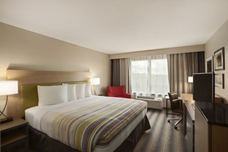 Spacious guest room with a king bed, flat-screen TV and red armchair