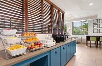 Hotel breakfast room with fresh fruit, a coffee station and blue cabinets