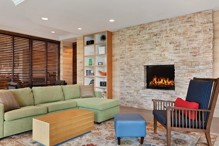 Welcoming hotel lobby with a fireplace, an armchair and a green sectional