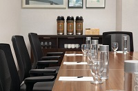 Hotel boardroom with black chairs, a long wooden table and a coffee station
