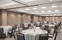 On-site ballroom featuring gray chairs and tables with white tablecloths arranged for a banquet