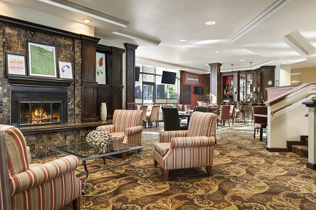 Sunnyvale hotel lobby with fireplace and striped armchairs