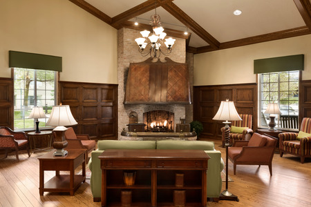 Welcoming lobby with a fireplace, chandelier, sofa and several armchairs