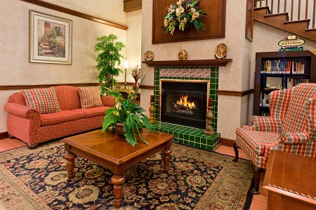 Welcoming lobby with a green-tiled fireplace, a sofa and a plaid armchair