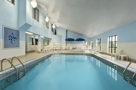 Sparkling indoor pool surrounded by white deck chairs