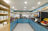 Breakfast servery with blue cabinets, fresh fruit, a waffle station and several juice flavors