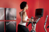 Woman using an elliptical in hotel fitness center