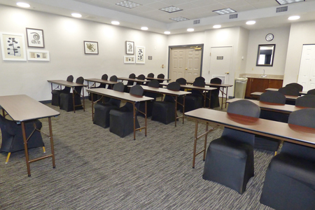Meeting room with tables and chairs in a classroom setup