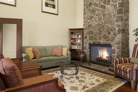 Lobby with couch, chairs, fireplace and books