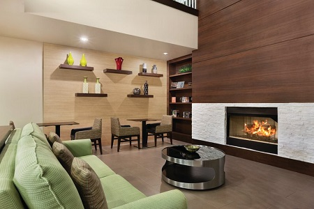 Welcoming hotel lobby with a green couch in front of a fireplace
