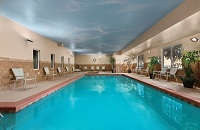 Indoor pool surrounded by patio chairs and potted plants