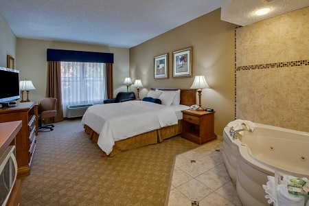 Hotel suite with a king bed and a whirlpool for two