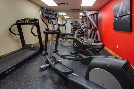 Fitness center with cardio equipment and red accent wall
