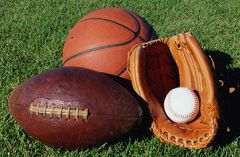 A football, a basketball and a mitt holding a baseball
