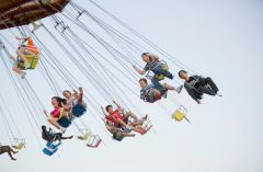 Amusement park guests on a swing ride