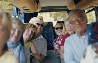 Group of elderly travelers riding on a tour bus