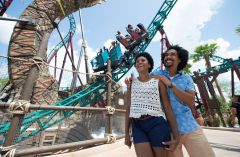 Smiling couple and roller coaster at Busch Gardens, Tampa, FL
