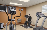 Fitness center with modern equipment and an orange accent wall
