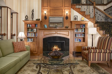Crackling fireplace flanked by wooden bookshelves
