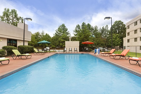 Sparkling outdoor pool with deck chairs and sun umbrellas