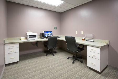 Printer, computer and two chairs in sleek hotel business center