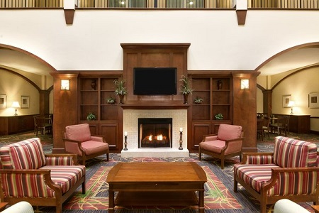 Welcoming hotel lobby with a fireplace and four armchairs