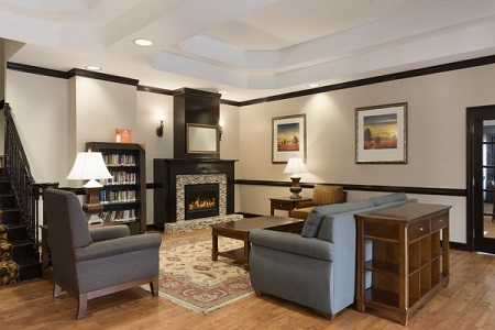 Lobby at the Country Inn & Suites in Buford includes fireplace and library
