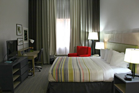 Guest room featuring a king bed with striped bedding and a red armchair