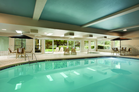 Indoor pool and hot tub with poolside tables and seating