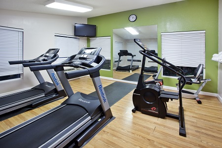 Fitness room with green wall and exercise machines