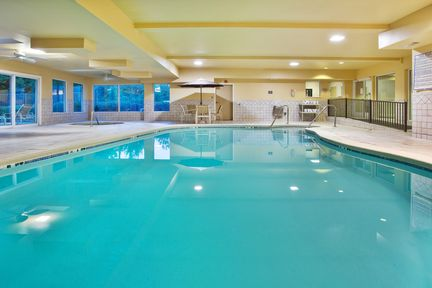 Indoor pool and hot tub area with yellow ceiling