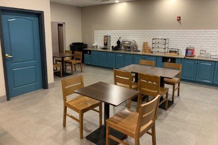 Breakfast room with blue cabinets, table seating and a make-your-own waffle station