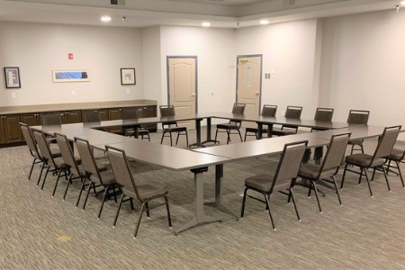 Meeting room with tables and chairs arranged in a hollow square