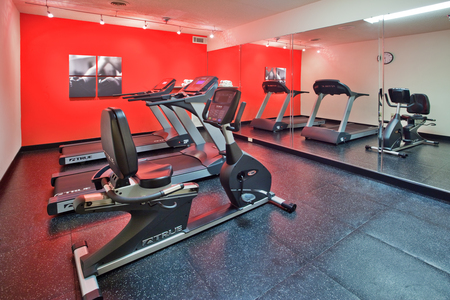 Hotel fitness center with bold colors and wall-length mirror