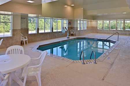 Indoor pool with handicap chair lift and white table and chairs