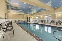 Indoor pool area with sky and clouds painted on ceiling