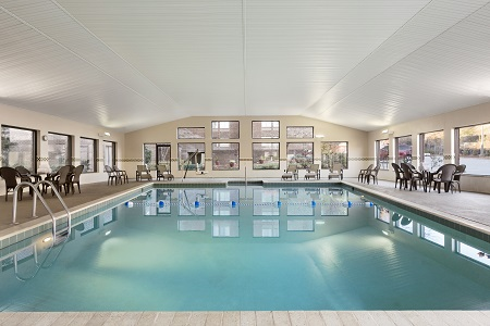 Indoor pool with chairs and windows