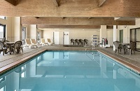 Indoor pool surrounded by lounge chairs and tables