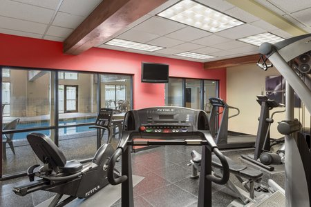 Fitness center with cardio equipment and views of the pool