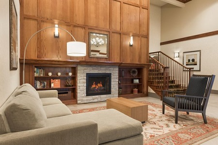 Spacious lobby with a fireplace, patterned rug and seating